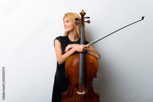 Young blonde girl with her cello posing on white wall Fototapete