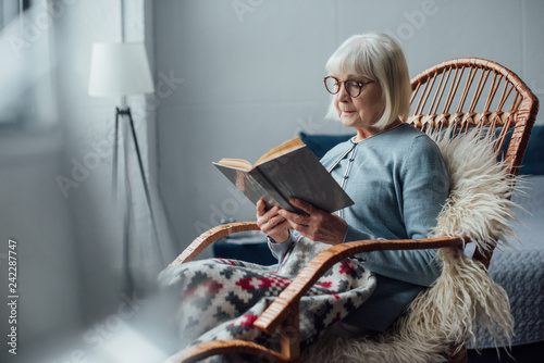 senior woman in glasses sitting in wicker rocking chair and reading book at home Canvas-taulu