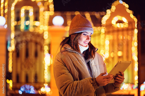 Fototapety, obrazy: A beautiful young woman or girl in jacket and gray hat using her digital tablet in the winter. Outdoor Christmas holidays background.