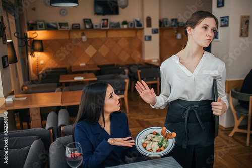 Fotografia, Obraz  Humble young businesswoman sit at table and show salad bowl to waitress