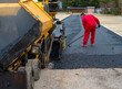 Worker regulate tracked paver laying asphalt heated to temperatures above 160 ° pavement on a runway