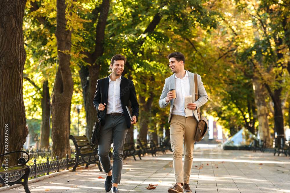 Fototapety, obrazy: Photo of bearded businessmen in suits walking outdoor through green park with takeaway coffee and laptop, during sunny day