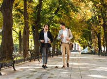 Photo Of Young Businessmen In Suits Walking Outdoor Through Green Park With Takeaway Coffee And Laptop, During Sunny Day