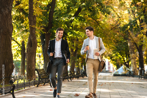 Obraz Photo of bearded businessmen in suits walking outdoor through green park with takeaway coffee and laptop, during sunny day - fototapety do salonu
