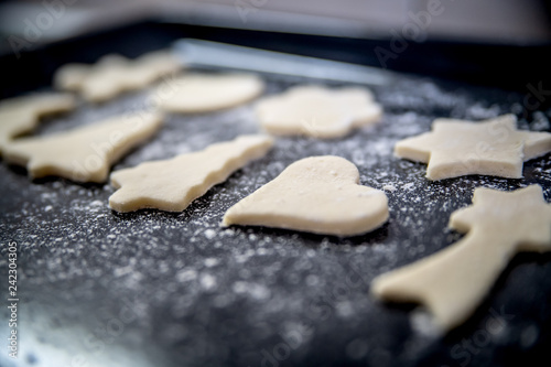 Biscuits of different shapes are lying on the tram and ready for baking.
