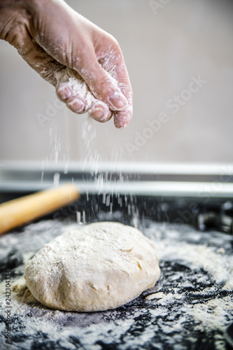 Fotografie, Obraz  Cook sprinkles dough lying on the table with flour.