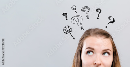 Hand draw question marks with young woman looking upwards on a gray background