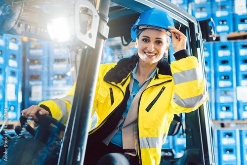 Photo  Arbeiter Frau fährt einen Gabelstapler in Logistik Lagerhaus