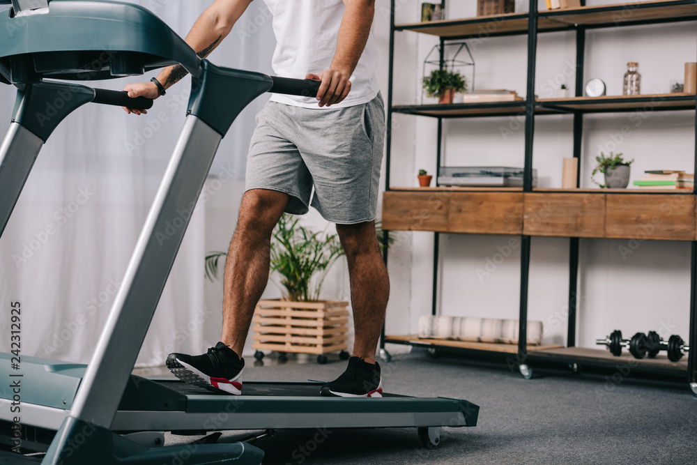 Fotografie, Obraz cropped view of man workout on treadmill in living room