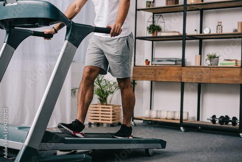 Fototapeta cropped view of man workout on treadmill in living room