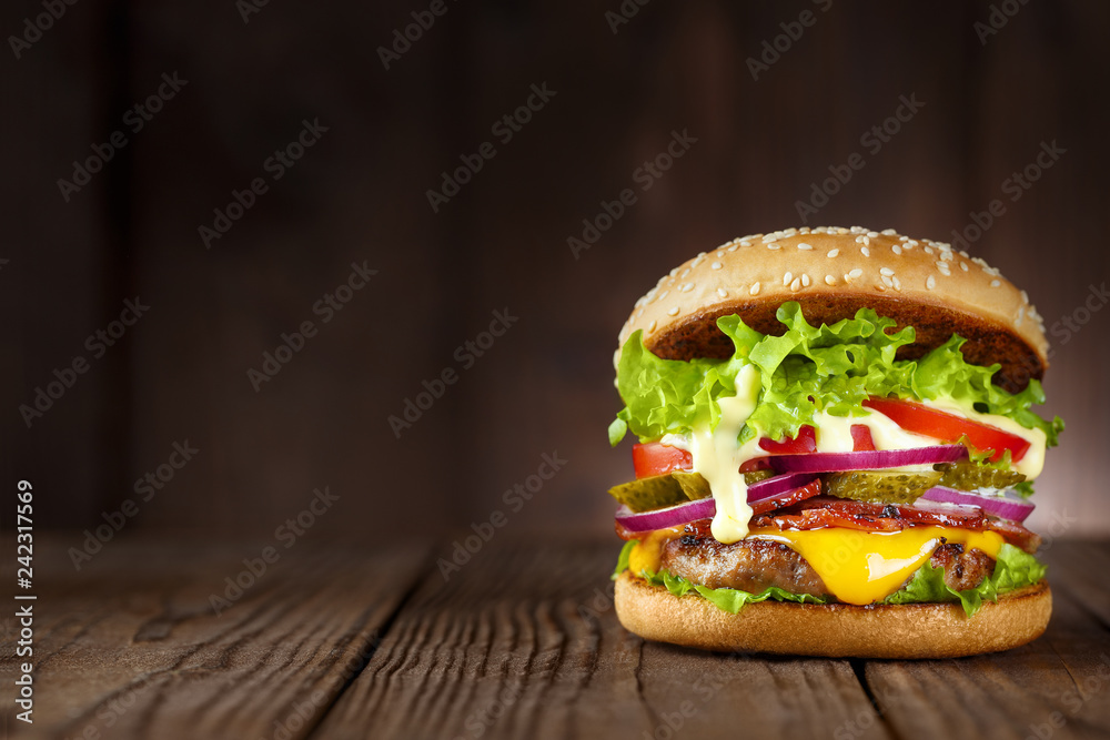 Fototapety, obrazy: Delicious burger with bacon, cucumbers, lettuce, cheese, onion and tomatoes on dark wooden background