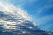 Feathery Clouds In The Blue Sky Are Illuminated By The Rays Of The Sun, Setting Over The Horizon