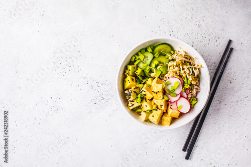 Foto  Vegan poke bowl with pickled tofu, vegetables and rice in a white bowl, top view