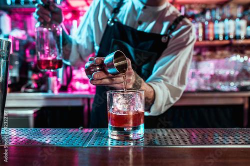 Foto Expert barman is making cocktail at night club or bar