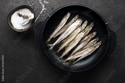 Photo Small sea fish smelt or sardine before cooking in a cast-iron form for baking with lemon, butter and salt
