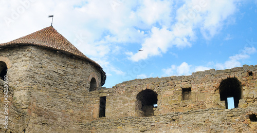 Foto  Fortress tower with tiled roof on blue sky background