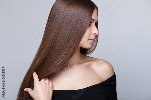 Beautiful young brunette woman with long straight hair and healthy glowing skin at studio on grey background Fototapet
