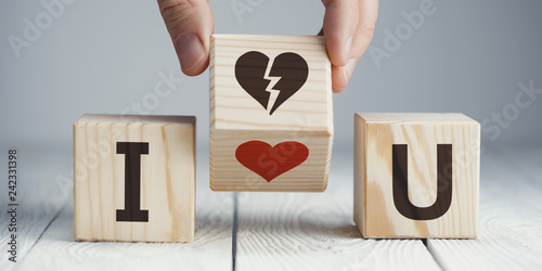 Photo Hand flipping a wooden cube to remove the red heart for the broken heart or vice