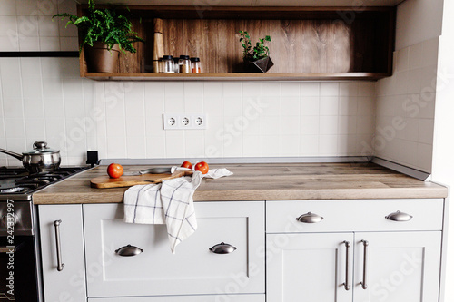 Fotografía  Cooking food on modern kitchen with steel oven, pots, knife on wooden cutting board with vegetables, pepper, spices,oil on wooden tabletop