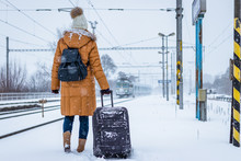 Travel By Train At Winter. Woman Standing On Railroad Station Platform And Looking At Arriving Train.