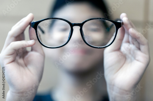 Cuadros en Lienzo The Black frame glasses on the hands of boys with short-sighted eyes in front