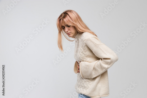 Fotografiet  Young cute woman in white sweater suffering from stomach ache, having menstruation pain, feels bad, abdominal cramps, side view