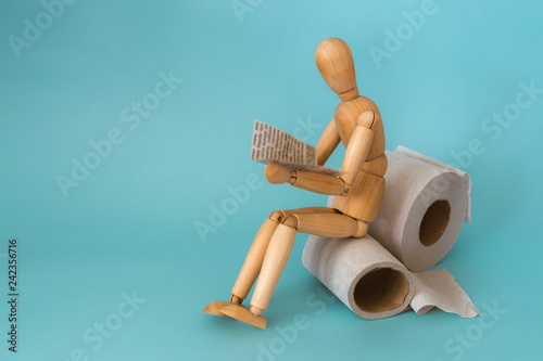Fotografia  Wooden figure sit on a roll of toilet paper and reading the newspaper
