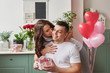 young couple in love at home celebrates Valentine's Day on February 14, a bouquet of red roses and heart-shaped balloons decorate the room