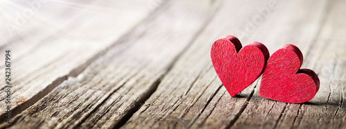 Two Wooden Hearts On Rustic Table With Sunlight