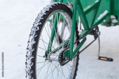 Photo Stands Bicycle Close - up of Bicycle wheel. Amsterdam, The Netherlands. Winter, Green trolley on a bicycle stands on white snow.