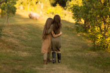 Two Girls Hug On The Street In The Forest. Friendship.back View