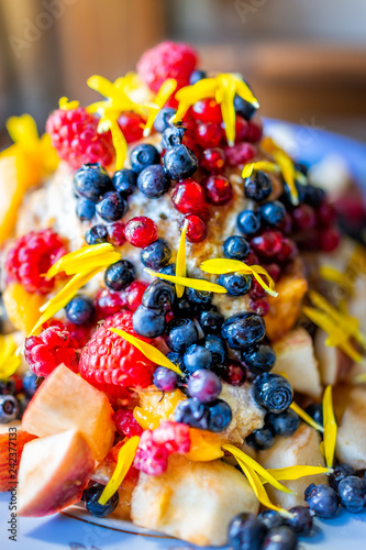 Fotografie, Obraz  Macro vertical closeup of colorful bowl of ice cream topped with vibrant blue bl