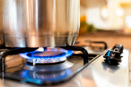 Canvas Prints Fire / Flame Macro closeup of modern luxury gas stove top with blue fire flame knobs and stainless steel pot with reflection and bokeh blurry blurred background