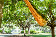 Closeup Of Orange Yellow Hammock In Savannah, USA With Famous Water Fountain In Forsyth Park, Georgia During Sunny Day In Summer Background