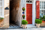 Fototapeta Sawanna - Charleston, USA downtown city street in South Carolina with nobody in southern town by old vintage houses architecture, narrow alley and door entrance