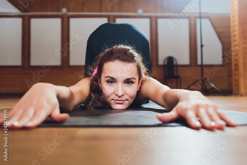 Fotografie, Obraz  Young attractive woman practicing yoga, doing asana paired with Cow Pose on the inhale, Cat exercise, Marjaryasana pose, working out, wearing sportswear, grey pants, top, indoor full length, studio