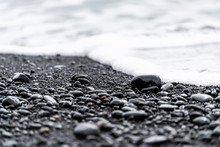 Closeup Of Large Black Volcanic Stones Or Pebbles On Sand Beach In Reynisfjara, Iceland With Water Waves Crashing On Shore To Shiny Wet Rocks