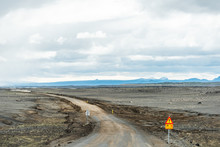 Dirt Road In North East Iceland Highlands Highway 864 To Dettifoss With Barren Brown Landscape Dust Car And Warning Sign On Cloudy Day And Volcanic Landscape