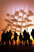 Silhouettes Of People Under The Famous Metallic Sculpture Umbrellas On Sunset, Thessaloniki, Greece.