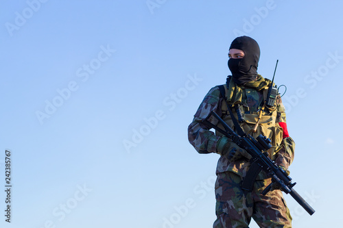 Fotografía  Airsoft soldiers are preparing to work in gloves, a camouflage military uniform, in a balaclava with a gun in their hands against the blue sky