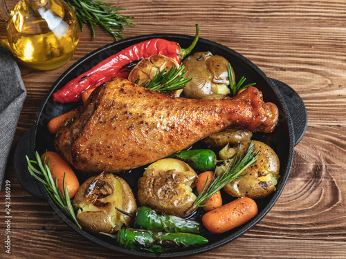 Foto Roasted turkey leg with vegetables, carrots, peppers, potatoes vegetables in fry