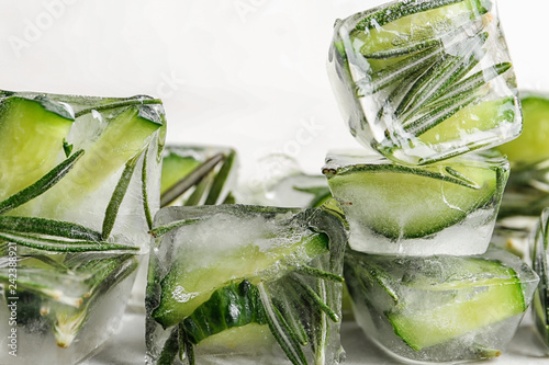 Ice cubes with cut cucumber and rosemary on light background, closeup