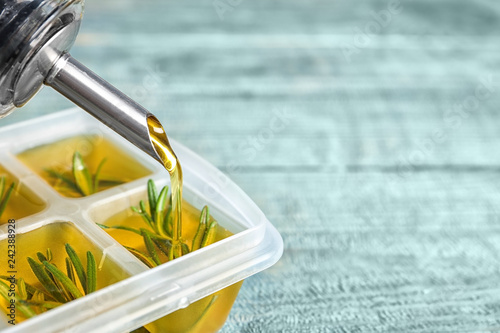Pouring olive oil into ice cube tray with rosemary on table, closeup. Space for text