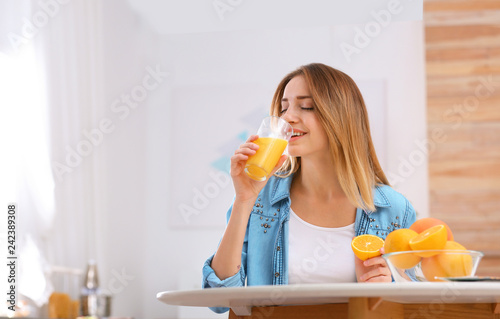 Beautiful young woman drinking orange juice at table indoors, space for text. Healthy diet