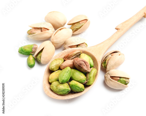 Organic pistachio nuts and spoon on white background, closeup