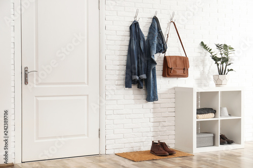 Fototapeta  Stylish hallway interior with door, comfortable furniture and clothes on brick w