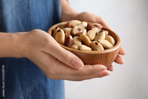 Woman holding bowl with Brazil nuts on grey background, closeup