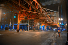 Deserted Downtown City Street Intersection Under A Vintage Railroad Train Subway Bridge At Night In Chicago