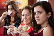 Three Generations Of Hispanic Women Drinking Coffee