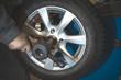 Repairman replaces and balancing car tyre wheel on special balancer equipment tool in car repair service